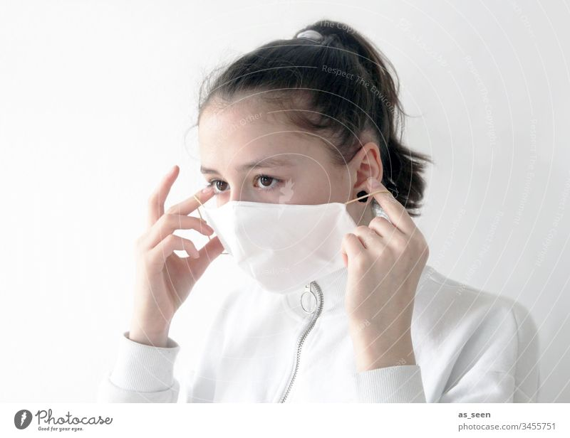 Girl puts on face mask Respiratory protection Respirator mask Mask Human being Colour photo 1 Fear Protection Threat Dangerous Illness coronavirus
