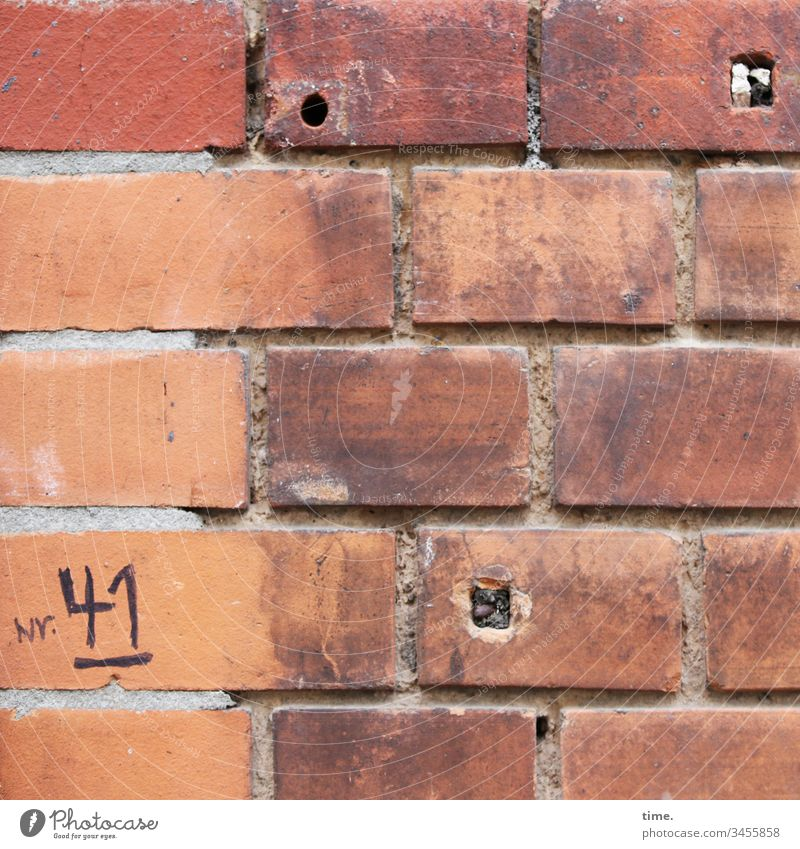 makeshift solution ::: handwritten house number on old badly grouted brick wall with 3 holes House (Residential Structure) Facade urban Stone daylight