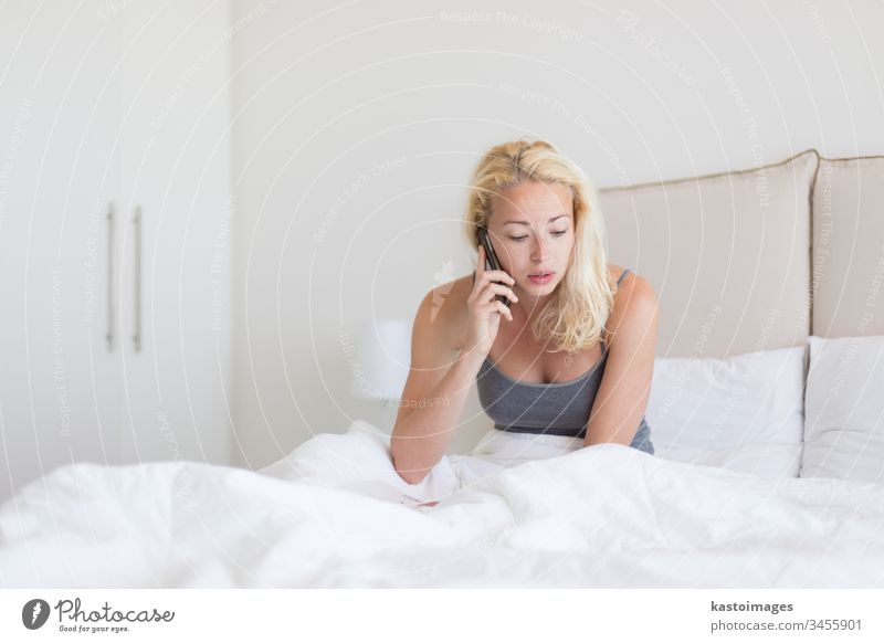 Woman talking by phone on bed in morning. woman call bedroom young person mobile white using pillows news home listening adult lonely interior wake motel