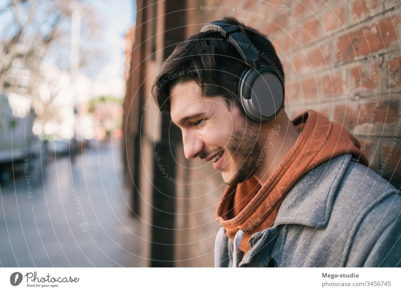 Latin man listening to music with earphones. person young people adult gadget outdoor technology lifestyle male casual alone sound entertainment city enjoying