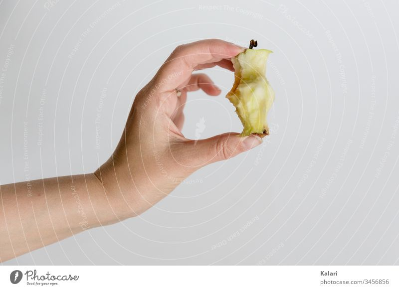 Hand holding core of an apple Core stop apples by hand salubriously Eating bitten off fruit Diet Juicy apple core Sweet White Healthy Fresh close up bitten into