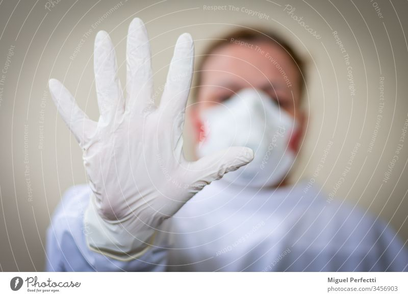 Nurse with protective mask and outstretched hand with a glove on advising to keep the safe distance so as not to get infected on a beige background doctor
