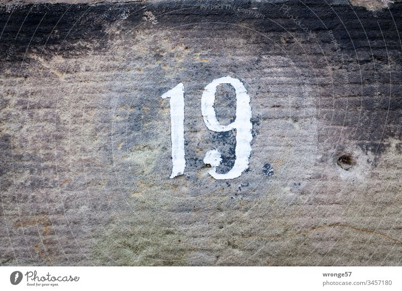 Figure 19 on a limestone wall Digits and numbers Close-up Exterior shot House number Orientation Colour photo Close-up view under natural lighting conditions