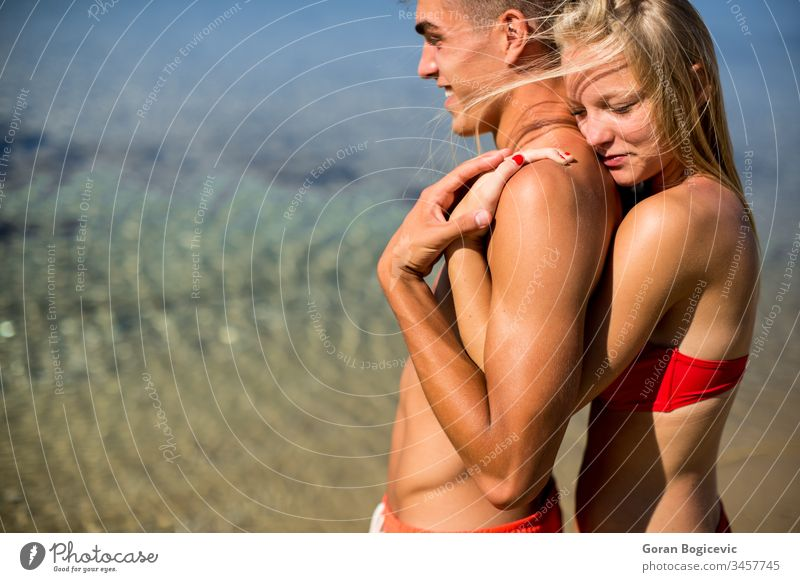 Young couple relaxing on the beach love happy summer women people sun sea holiday vacation relationship young lovers lifestyle male ocean together two romance