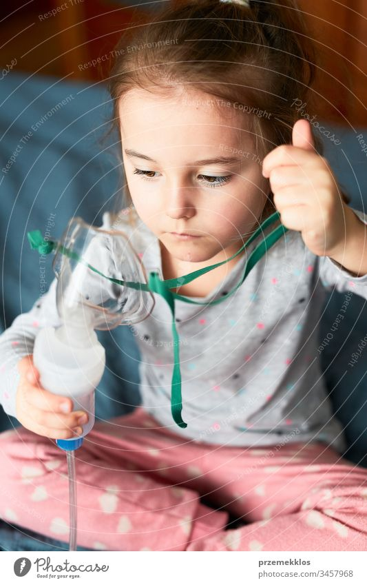 Sick little girl having medical inhalation treatment with nebuliser. Child holding breathing mask sitting in bed child virus infection doctor flu ill sick cold