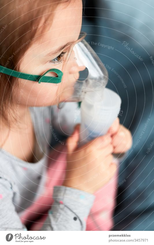 Sick little girl having medical inhalation treatment with nebuliser. Child with breathing mask on her face sitting in bed child virus infection doctor flu ill