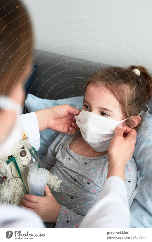 Doctor covering little patient's face with mask. Sick girl having medical inhalation treatment with nebuliser child virus infection doctor flu ill sick cold