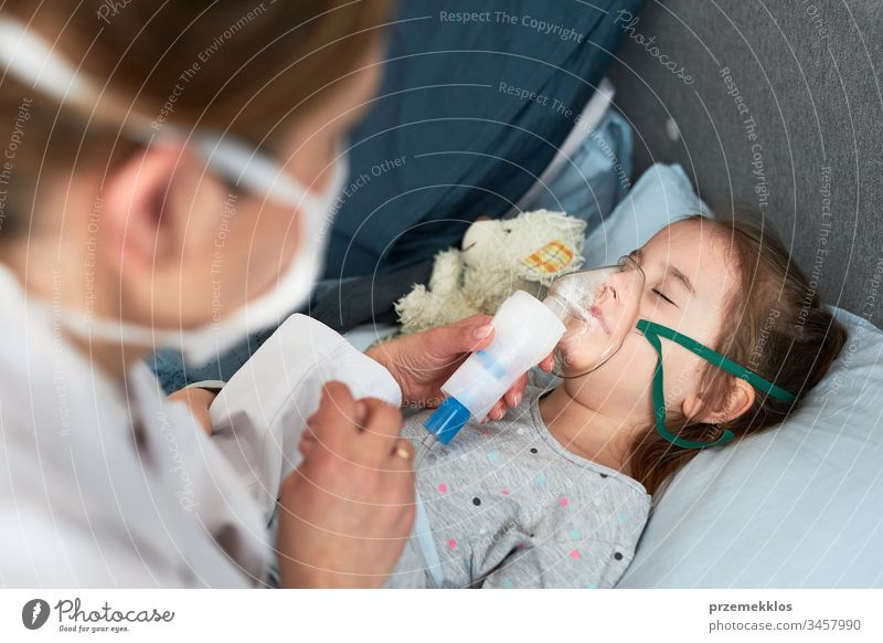 Doctor visiting little patient at home. Child having medical inhalation treatment with nebuliser. Girl with breathing mask on her face. Woman wearing uniform and face mask