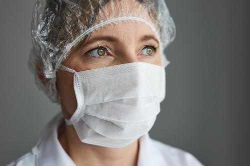 Doctor with face covered with mask. Portrait of young woman wearing the uniform, cap and mask to avoid virus infection and to prevent the spread of disease. Real people, authentic situations