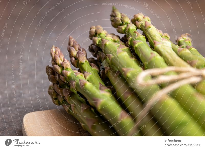 A bunch of green asparagus on a wooden board Asparagus Vegetable Food Nutrition Vegetarian diet Healthy Eating Organic produce Green Fresh Deserted Close-up