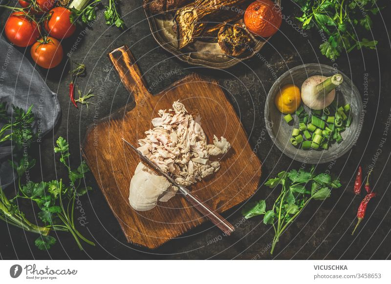 Pulled chicken breast on cutting board with knife with vegetables ingredients on dark rustic background. Top view. Healthy food eating. Low carb fitness dieting. Easy cooking