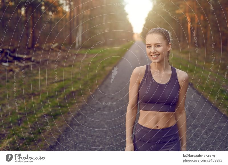 Smiling athletic fit young woman working out on a tarred lane through forests backlit by the warm glow of the sun in a healthy active lifestyle concept face