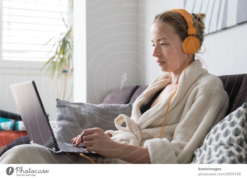 Stay at home and social distancing. Woman in her casual home bathrobe working remotly from her living room. Video chatting using social media with friend, family, business clients or partners.