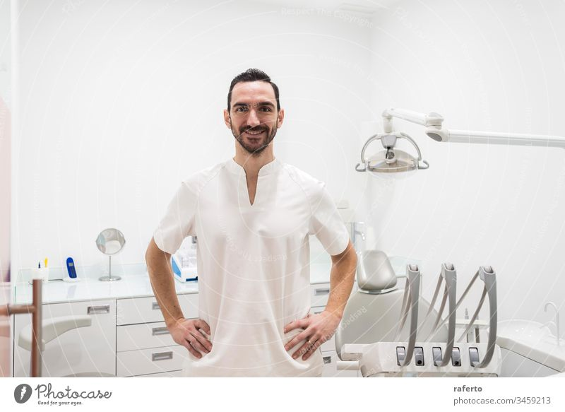 Portrait of a smiling doctor male posing in an dentist office clinic happy portrait health care dental bearded professional dentistry white job hospital