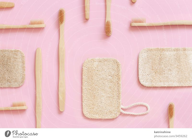 Eco friendly bamboo toothbrushes and dish washing sponges on pink background waste concept light pink top view zero waste Loofah tooth brushes eco health