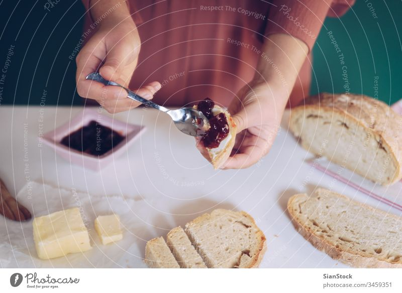 Womans hand spreads jam on homemade bread making kitchen green background dress marble toasted spoon table calories eating young protein jar peanut jelly