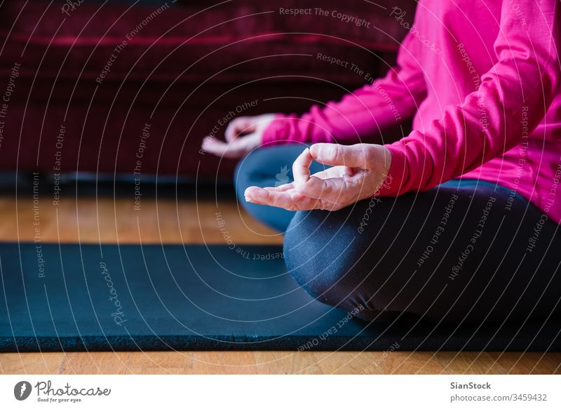 Hands close up of middle aged woman sitting in lotus position on yoga mat in her living room. bending beauty workout european exercising hands flexibility