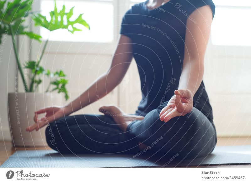 Woman doing yoga in the morning at her home. mat woman fitness young lotus pose asana beautiful sport health exercise workout wellness gym female girl pilates