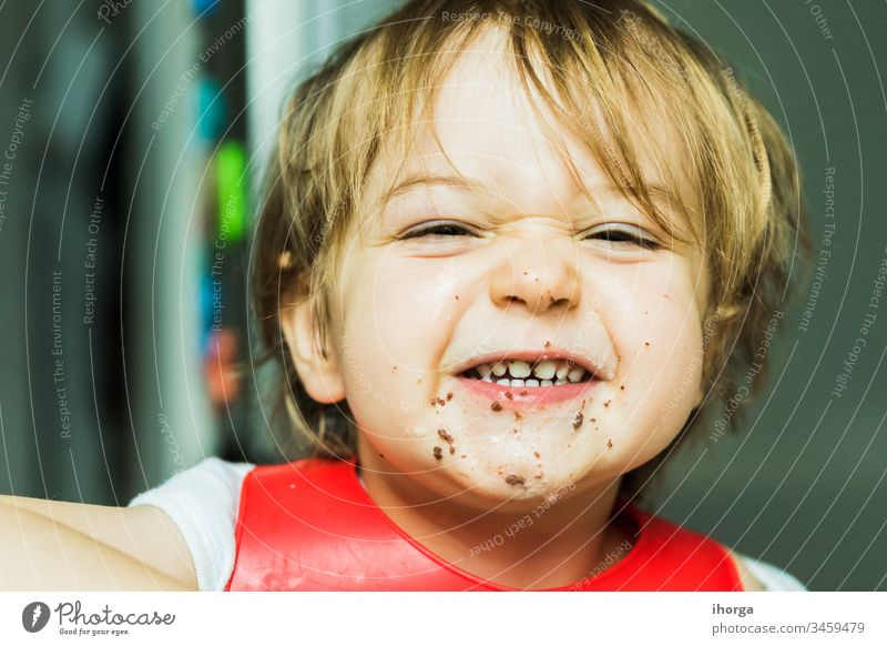 portrait adorable child eating chocolate sponge cake attribute baby background bib boy brown candy childhood cute delicious desert dessert dirty fat flavour