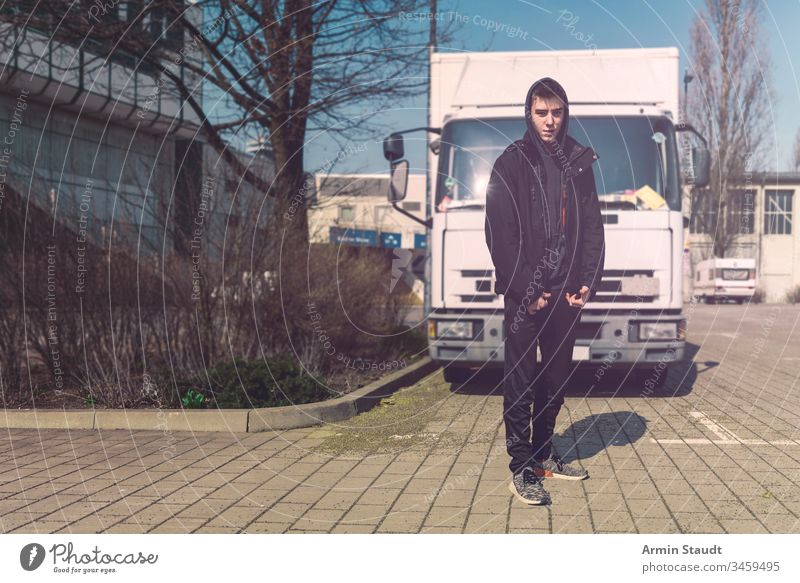 young man with backpack stands in front of a truck teenager lifestyle lorry portrait aeria architecture beautiful black boy building casual caucasian confident