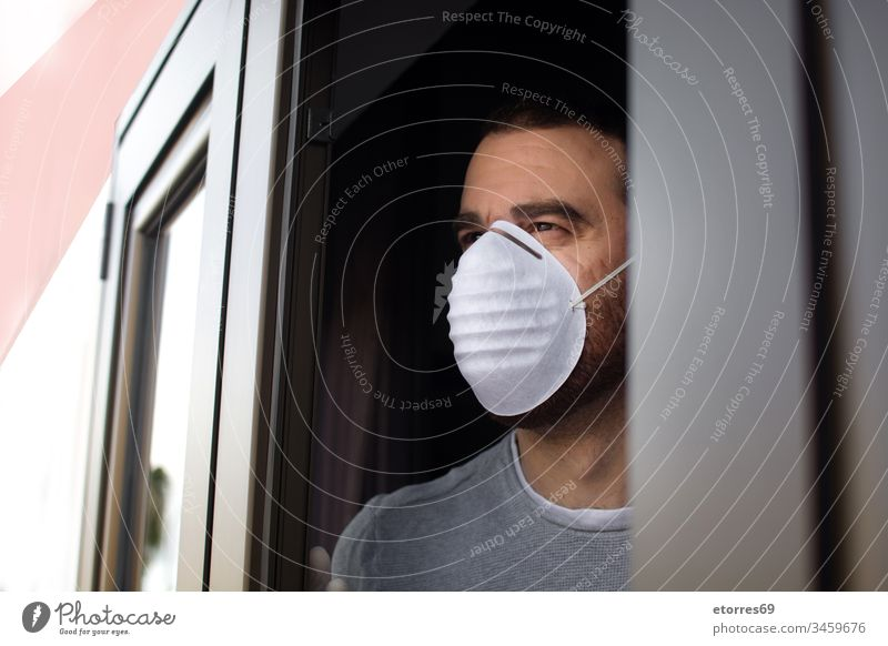 Man with face mask and gloves looking out the window man coronavirus quarantine covid-19 confinement disposable stay at home care caucasian concept health house