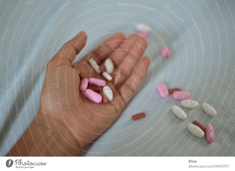 A hand in which several different colored tablets are lying; addiction problems, drug abuse, suicide drugs pills variegated Addiction Dependence Medication Pill