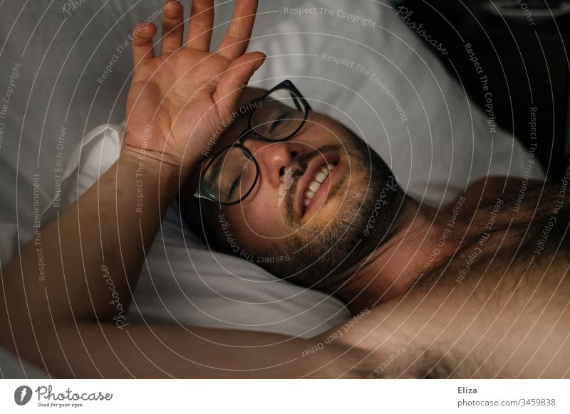 A man with a beard and glasses, who lies comfortably and sleepily in bed and touches his forehead with his hand Man Bed Eyeglasses Facial hair Forehead Hand