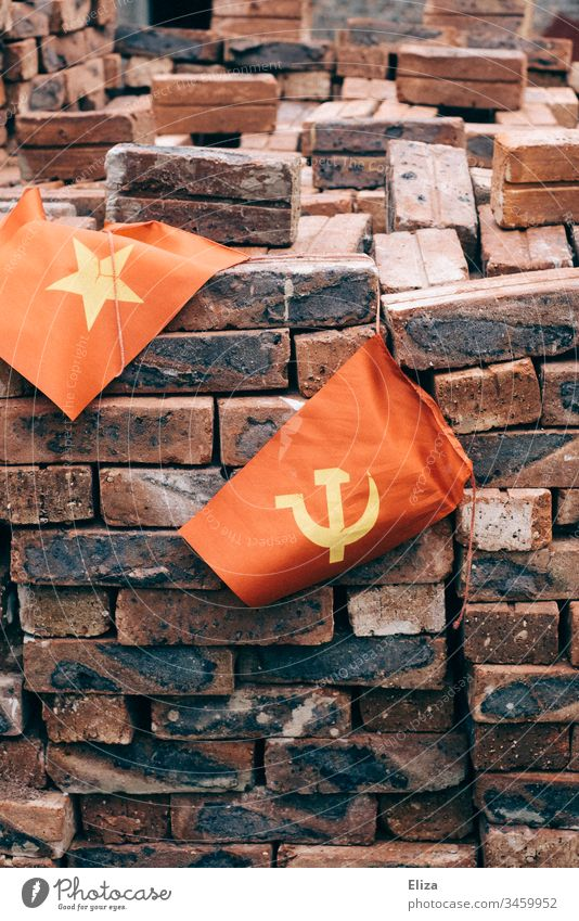 The Vietnamese flag next to a flag with hammer and sickle, symbolizing the communist state, in front of a pile of red bricks Communism Hammer Socialism Build
