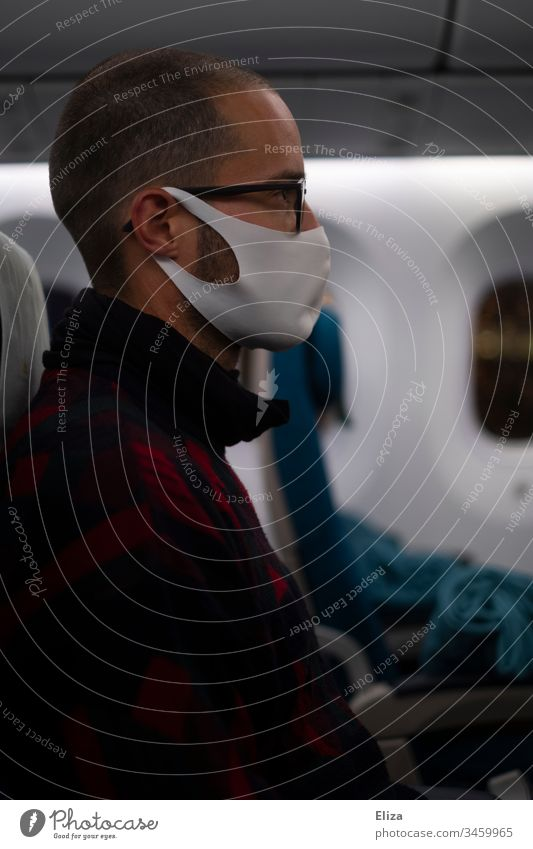 Man sitting in a plane with a face mask during the Corona Pandemic Airplane corona pandemic Face mask Mask fabric mask coronavirus prevention Virus COVID