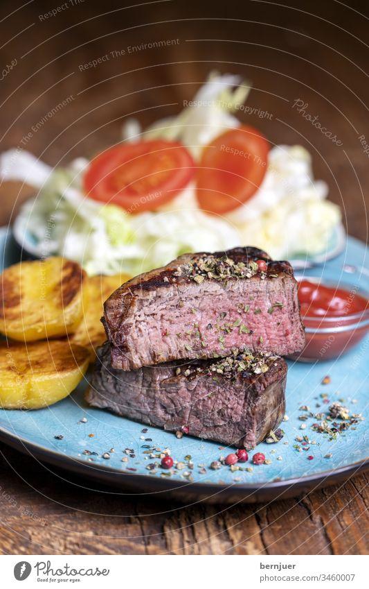 Grilled steak on the plate Filet mignon Steak Slice half Half habliert potato Lettuce Tomato Resources Ketchup greaseless BBQ Dinner Meal Salt herbaceous