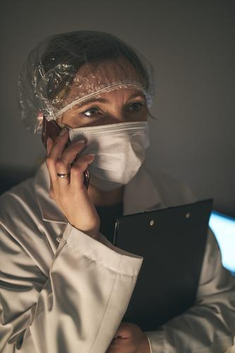 Doctor making a phone call. Hospital staff working at night duty. Woman wearing uniform, cap and face mask to prevent virus infection doctor flu ill sick care