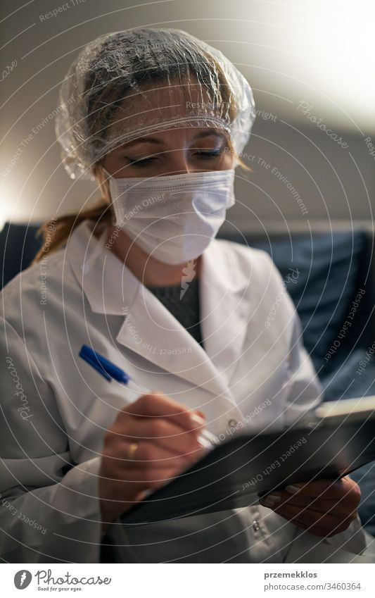 Doctor filling out a document. Hospital staff working at night duty. Woman wearing uniform, cap and face mask to prevent virus infection doctor flu sick care