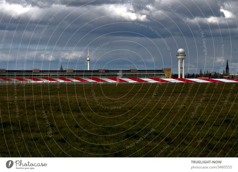 Berlin Tempelhofer Feld of the disused airport on a gloomy cloudy day with a view of a red and white barrier tape, the main building and the Berlin television tower in the background