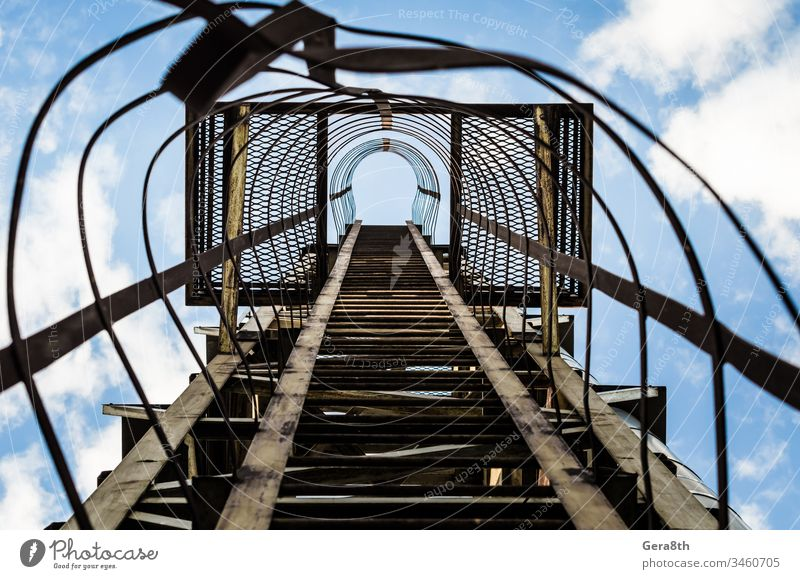 old rusty staircase with damages against the blue sky and clouds climb gray grunge industrial iron iron staircase ladder line lines metal overlap perspective