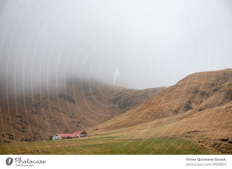 Hillside house in Iceland cropland dawn driving europe excursion fog grass hay hill landscape light meadow mist mountain movement nature no person outdoors