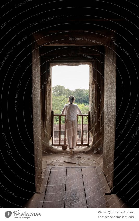woman looking out the window in a temple Angkor Cambodia Siem Riep architecture asia bright castle door doorway family house indoors light lumber luminous