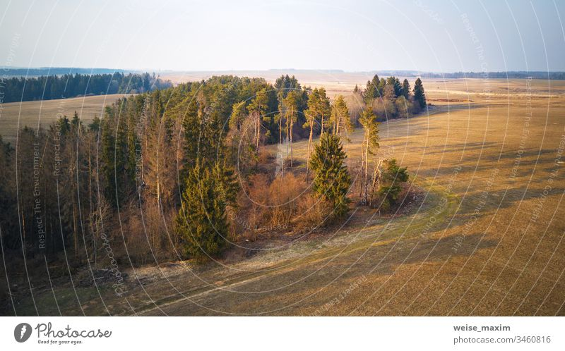 Sunny March-April evening scene. Calm spring countryside sunset Panorama aerial field agriculture cultivated plowed rural industrial sunny wood forest pine