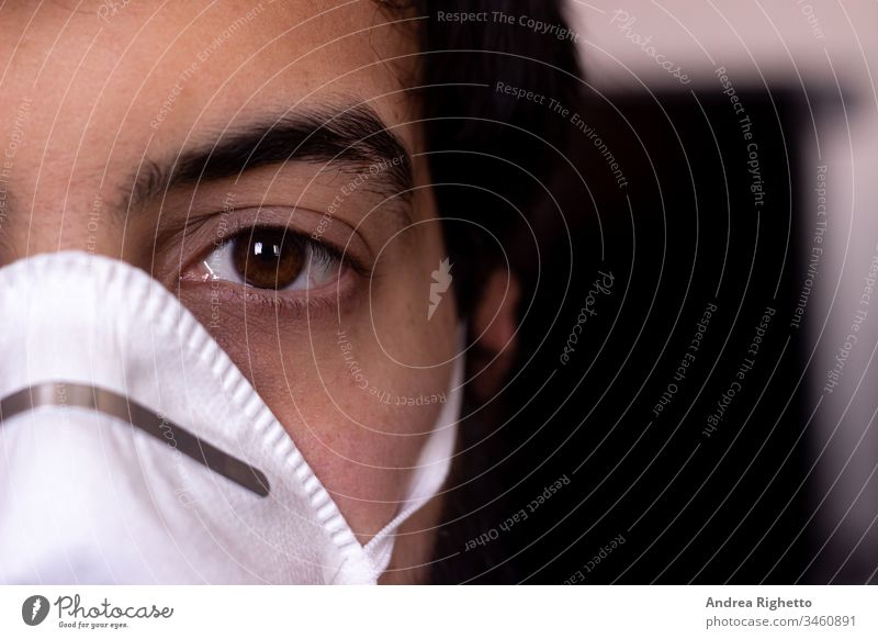 Half portrait of a young caucasian adult wearing a white mask. Copy space on the right. Man looking at the camera air boy care closeup coronavirus covid19