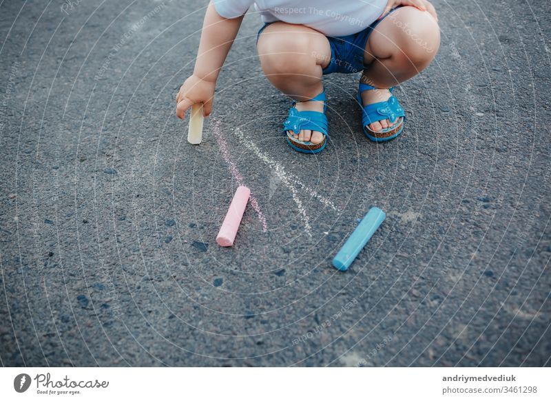 Close up of little girl drawing with chalks on the sidewalk color hand pavement art summer background colorful fun outdoor child park leisure small kid play