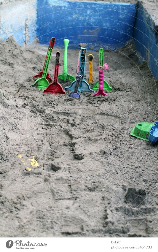 Many, colourful plastic sand shovels are stuck in the sand, in an empty sandbox of stone, on holiday. Sand Sandpit Sandal shovel Shovel Playing Toys Infancy