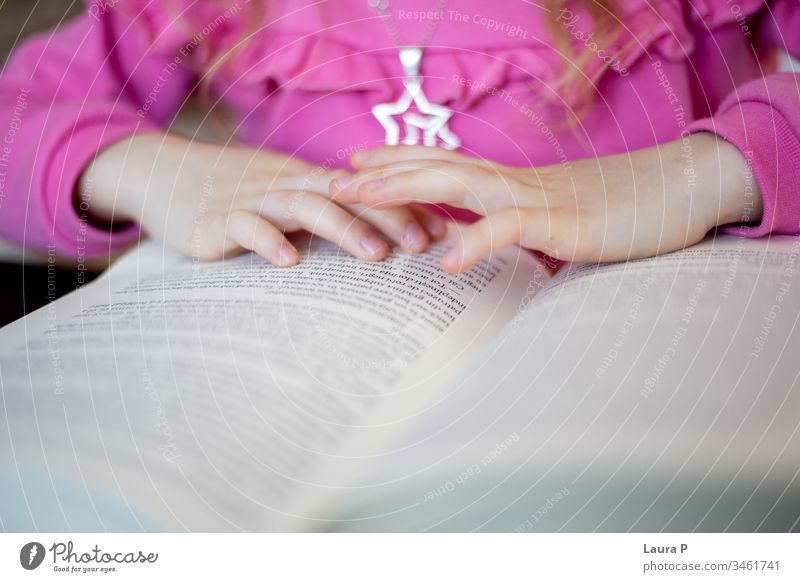 Close up of little girl's hands reading adorable attentive attentively beautiful blonde book bored caucasian child childhood clever closeup concentrated cute