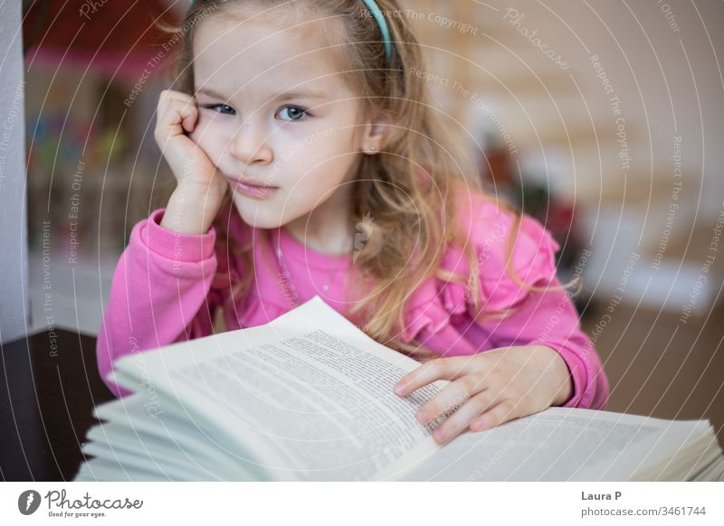 Little blonde girl tired and bored of reading and doing homework adorable attentive attentively beautiful book caucasian child childhood clever closeup