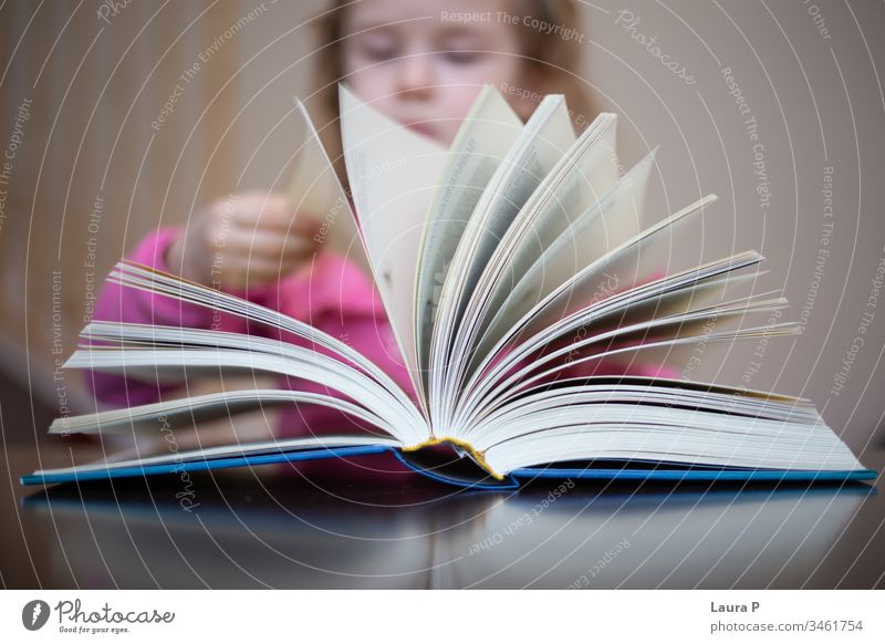 Little blonde girl  reading and doing homework adorable attentive attentively beautiful book bored caucasian child childhood clever closeup concentrated cute