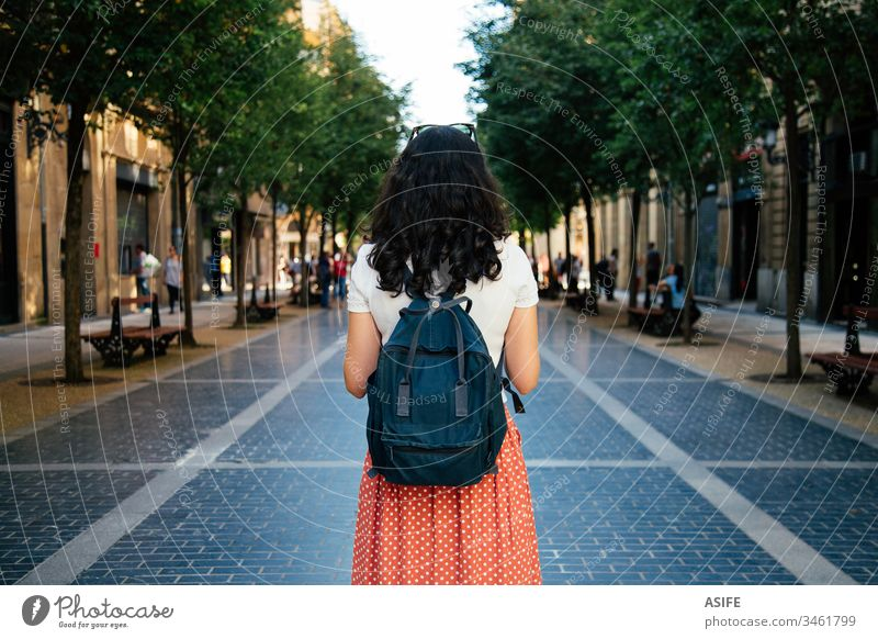 Tourist woman travelling alone tourist vacation girl holiday city happy backpack summer spring people rear view back view brunette Europe map lifestyle street