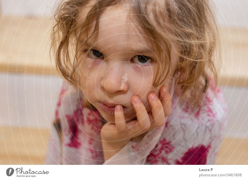 Close up of an upset little blonde girl holding her chin in her hand adorable alone angry bad mood beautiful bored child childhood cute emotion emotional