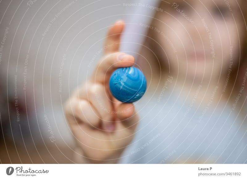 Close up of child fingers holding a small blue ball blurred background close up family time play showing pressing joy color care girl cheerful children toddler