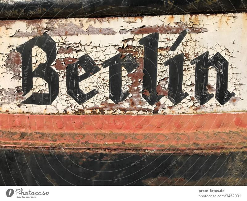 Flaking Berlin lettering on metal. Capital city Germany Typography Federal capital Metal Black White Red ship boat Rust age Yellowed Varnish Varnished paint