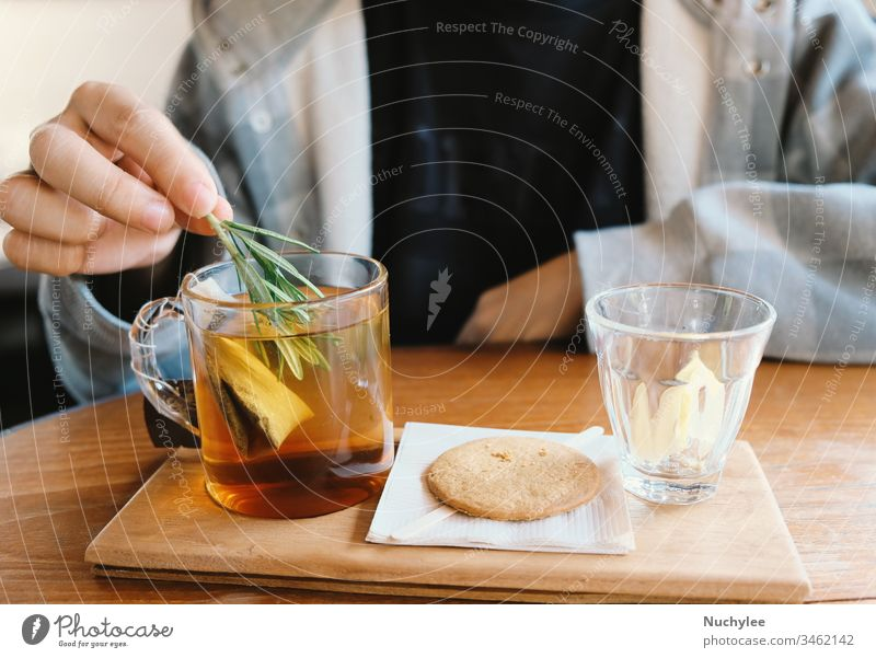 Close up young man hand putting rosemary into the hot tea for afternoon tea time break, relaxing and cozy at home aromatic asian background beverage bowl