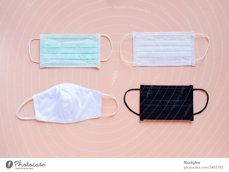 Flat lay of various kind and color of hygienic masks on bright pastel peach orange color background, health care and prevent the spread of pandemic Covid-19 and Coronavirus,