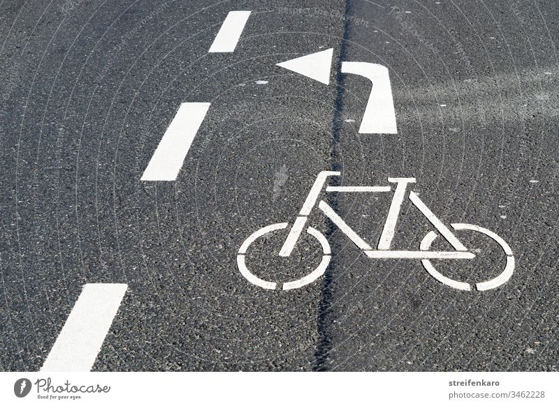Cyclists please turn left through the gap, the white arrow of the road marking meant Street Traffic lane Road marking Lane markings White Gray Asphalt Cycling